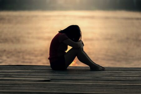 Lány szomorúan ül a stégen