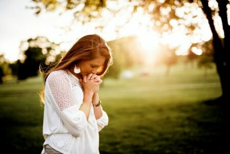 Kezét összekulcsolva imádkozó nő